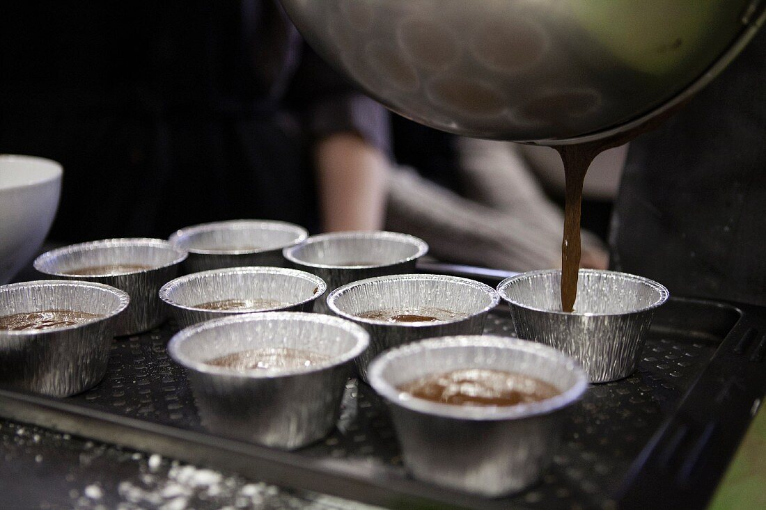 Chocolate mixture being poured into aluminium moulds