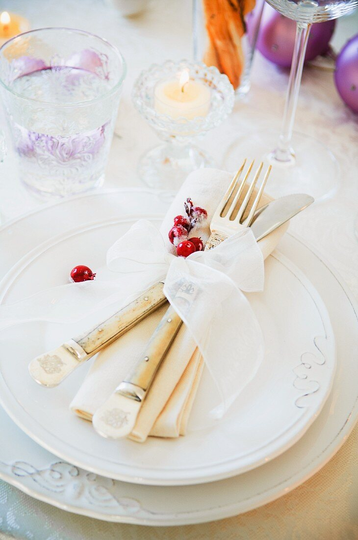 A Christmas place setting with cutlery, a napkin and a ribbon
