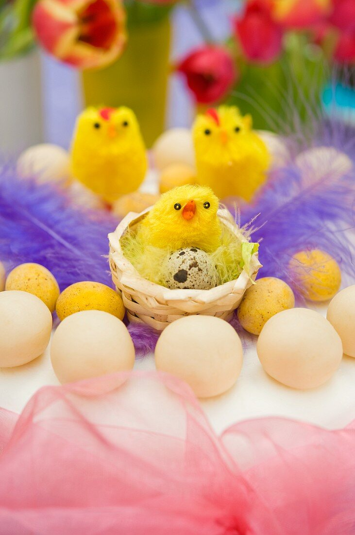 still life arrangement of Easter simnel cake with pink chiffon ribbon and yellow chicks with spring tulips
