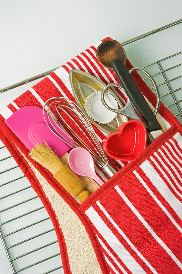 close up overview of a red and white striped oven glove filled with cooking utensils on an oven tray