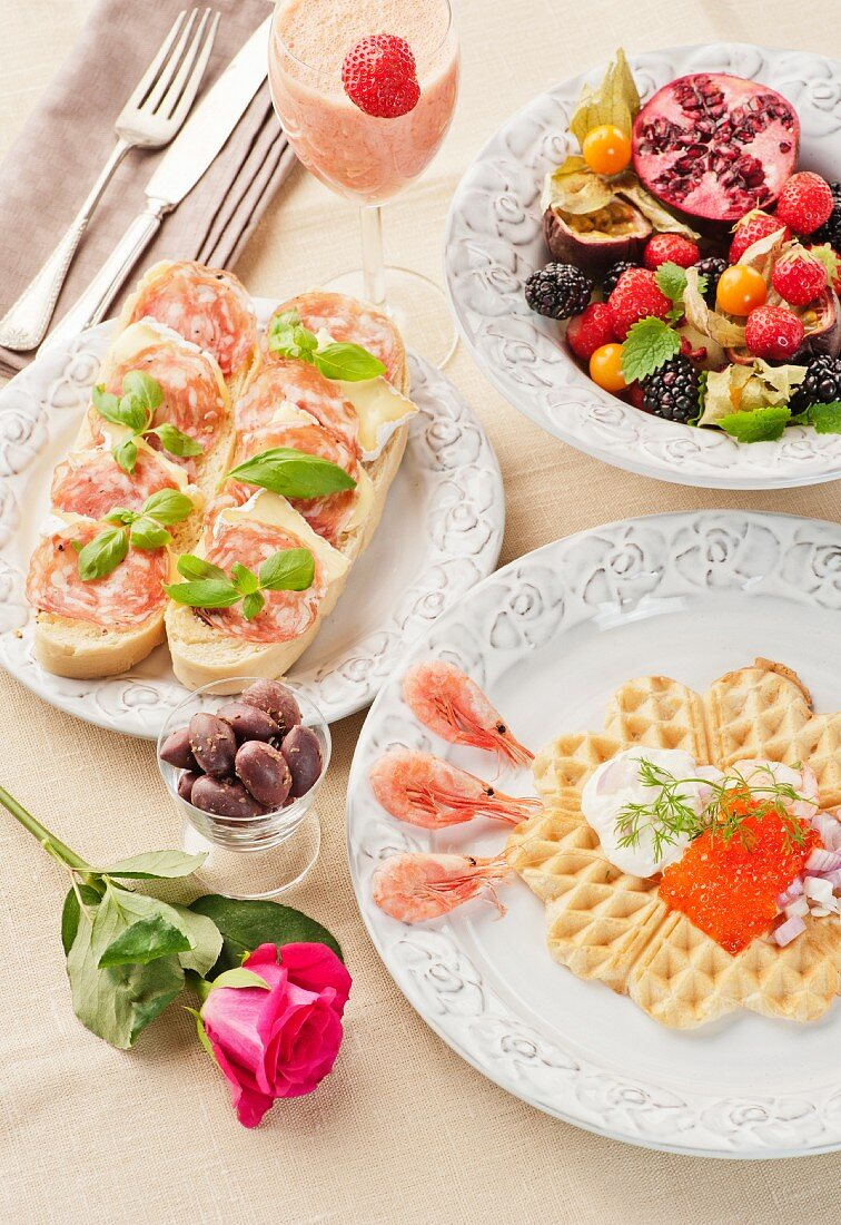 A breakfast of a caviar-topped waffle, slices of bread topped with cheese and ham, fresh fruits and a strawberry and mango smoothie