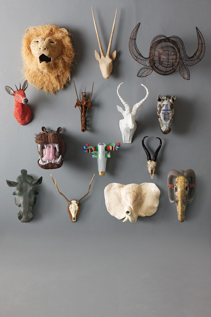 Miniature hunting trophies hanging on a grey wall
