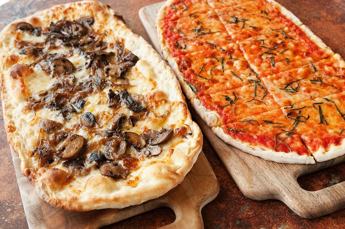 Two Pizzas on Cutting Boards;One Mushroom and One Cheese