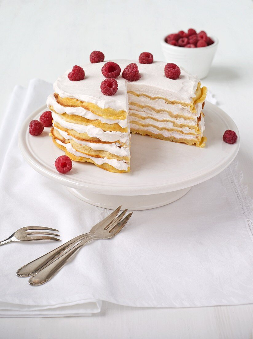 Waffle layer cake with raspberries, one slice removed