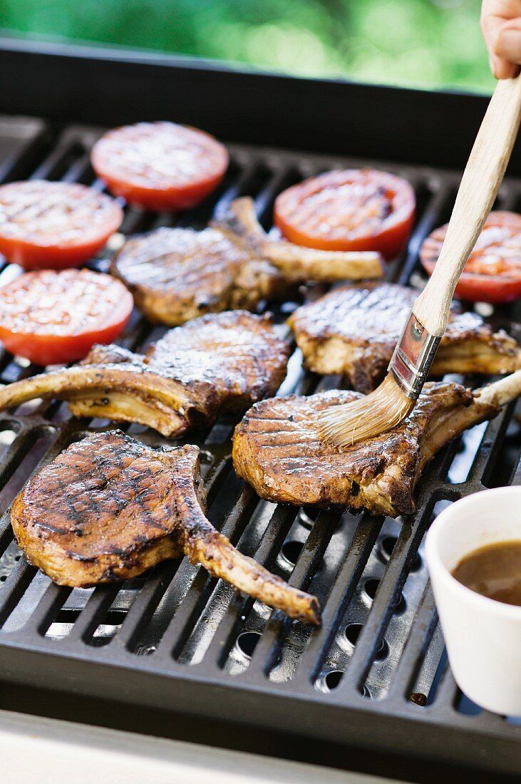 Lamb chops being brushed with marinade on the barbecue