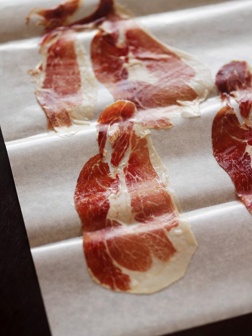 Thin Slices of Spanish Pata Negra Ham on Parchment Paper