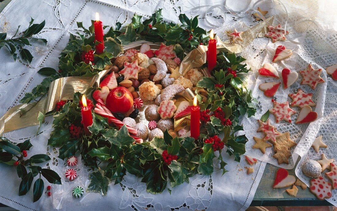A Christmas wreath made of holly and ivy with candles, filled with biscuits (vanilla crescents, pecan balls, ginger and coconut macaroons)