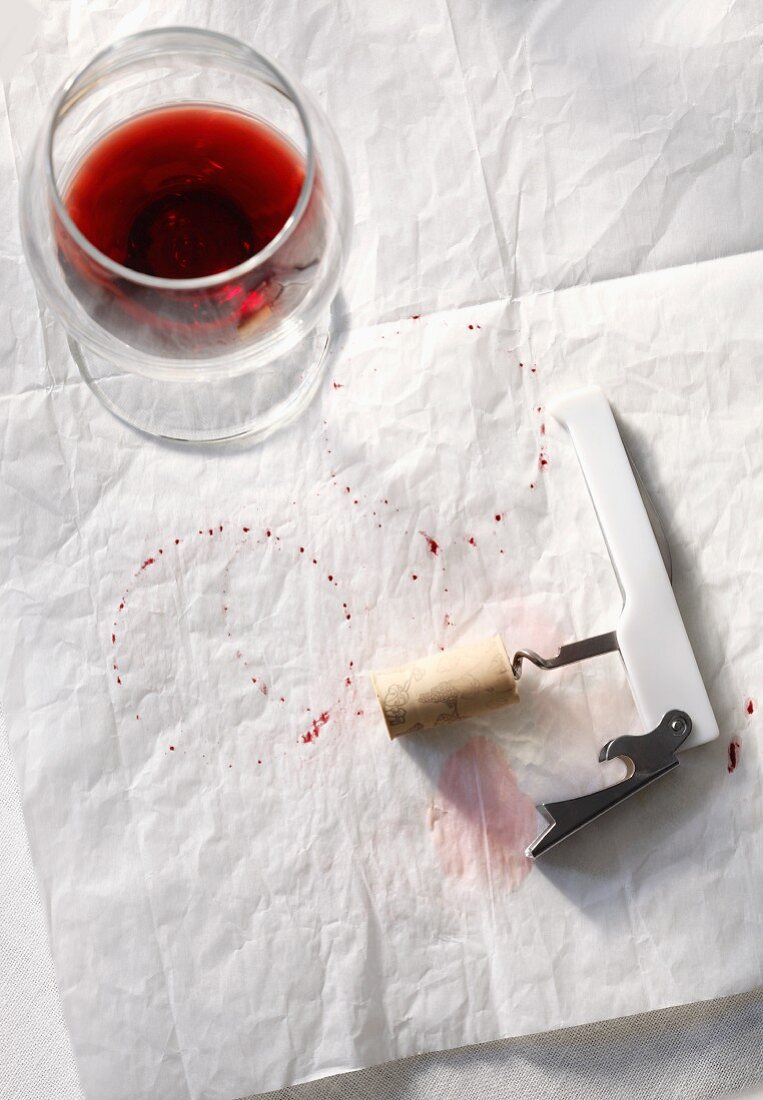 Half Empty Glass of Red Wine with Corkscrew and Wine Stains on Paper