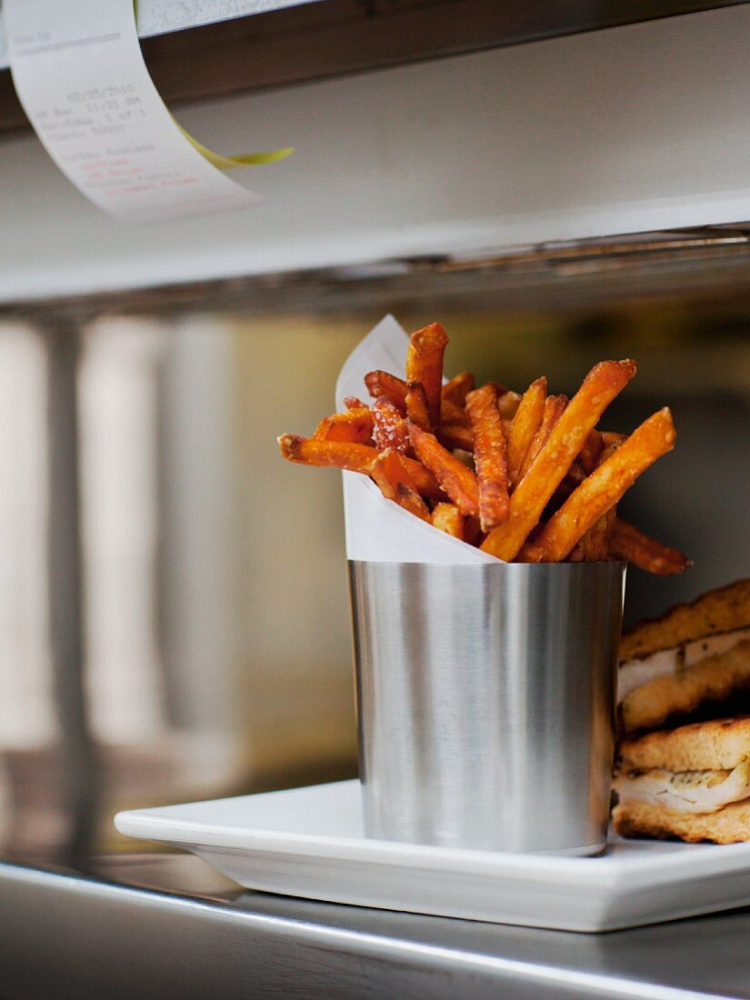 """Seasoned Fries with Wax Paper in a Steel Cup on a Restaurant """"Order-Up"""" Counter"""