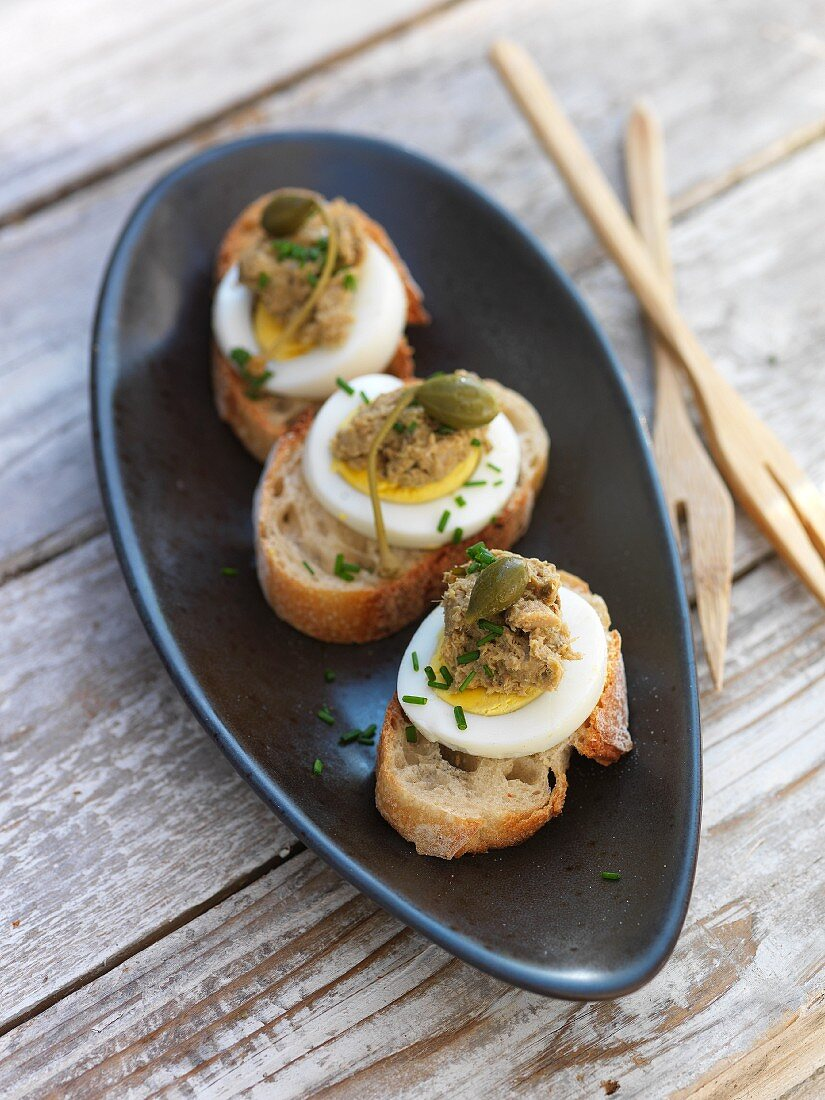 Mini open sandwiches topped with egg, anchovy paste and capers