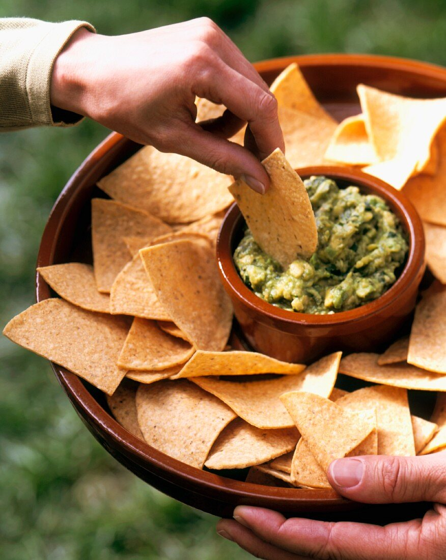 Hand Dipping a Tortilla Chip into Chunky Guacamole; Outdoors