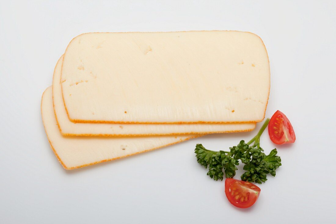 Three slices of Butterkäse (mild, semi-soft cheese), with parsley and sliced tomatoes