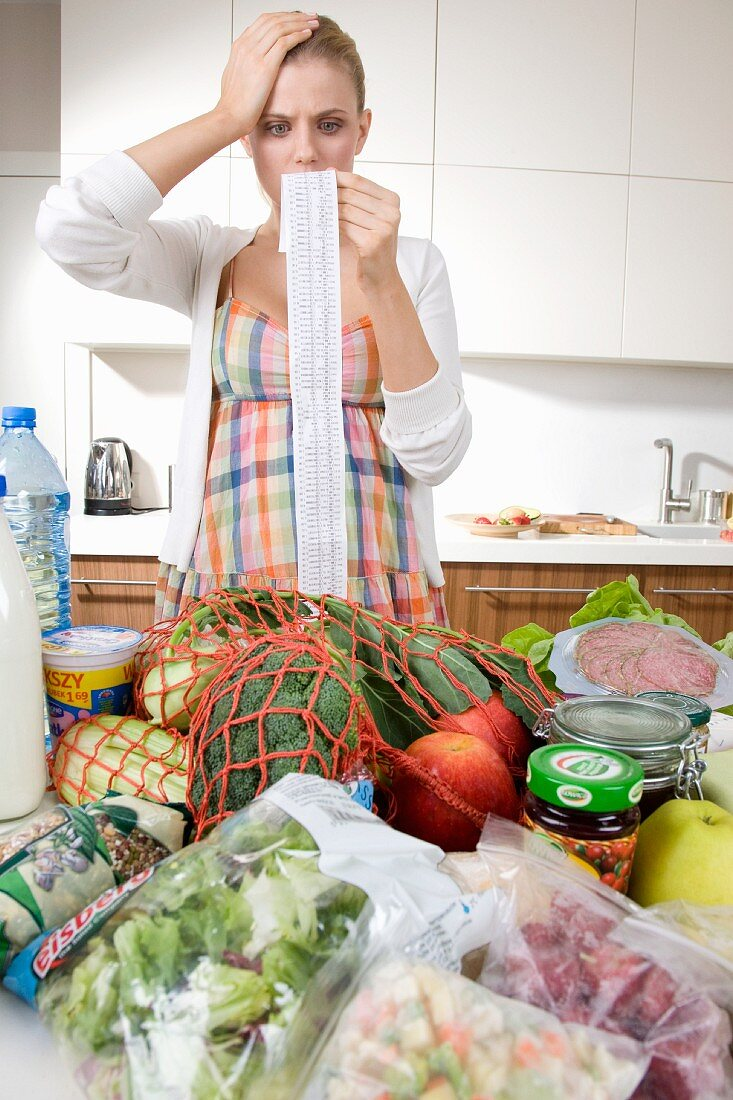 A woman checking a shopping bill in the kitchen