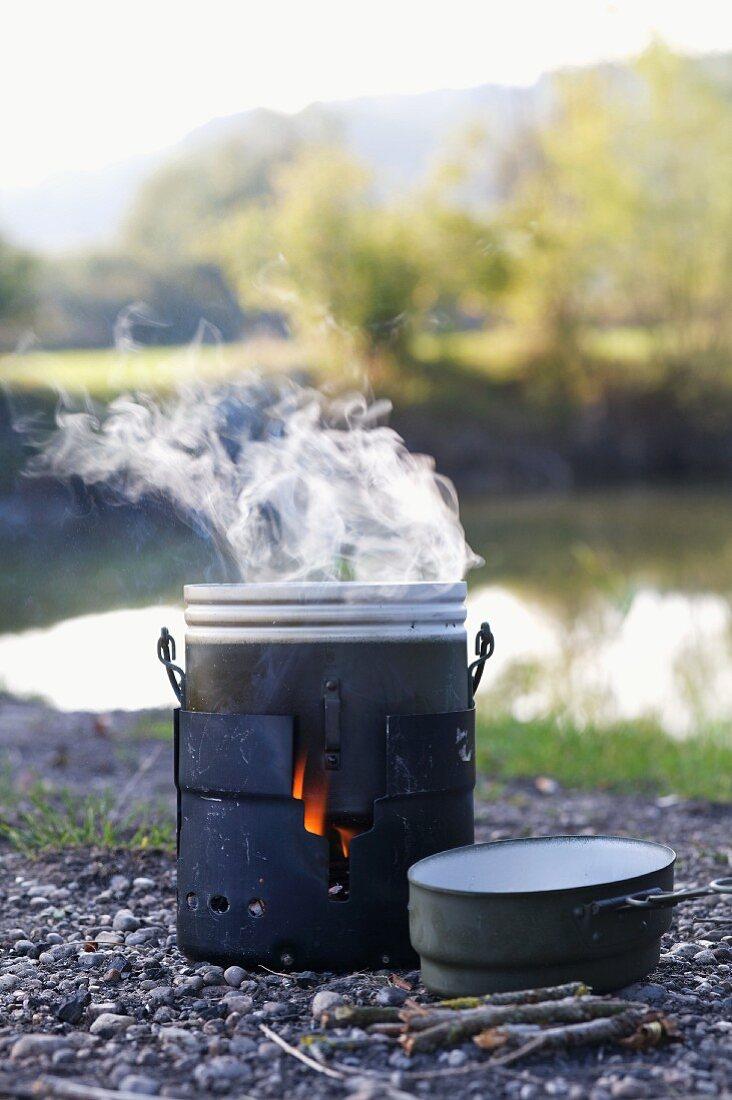 A smoking hobo oven on the bank of a lake