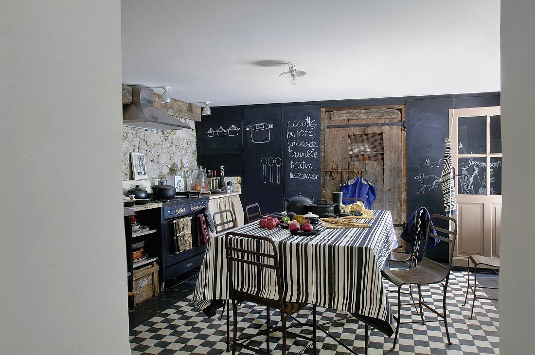 Rustic kitchen with blackboard, wooden door, dining table and chairs