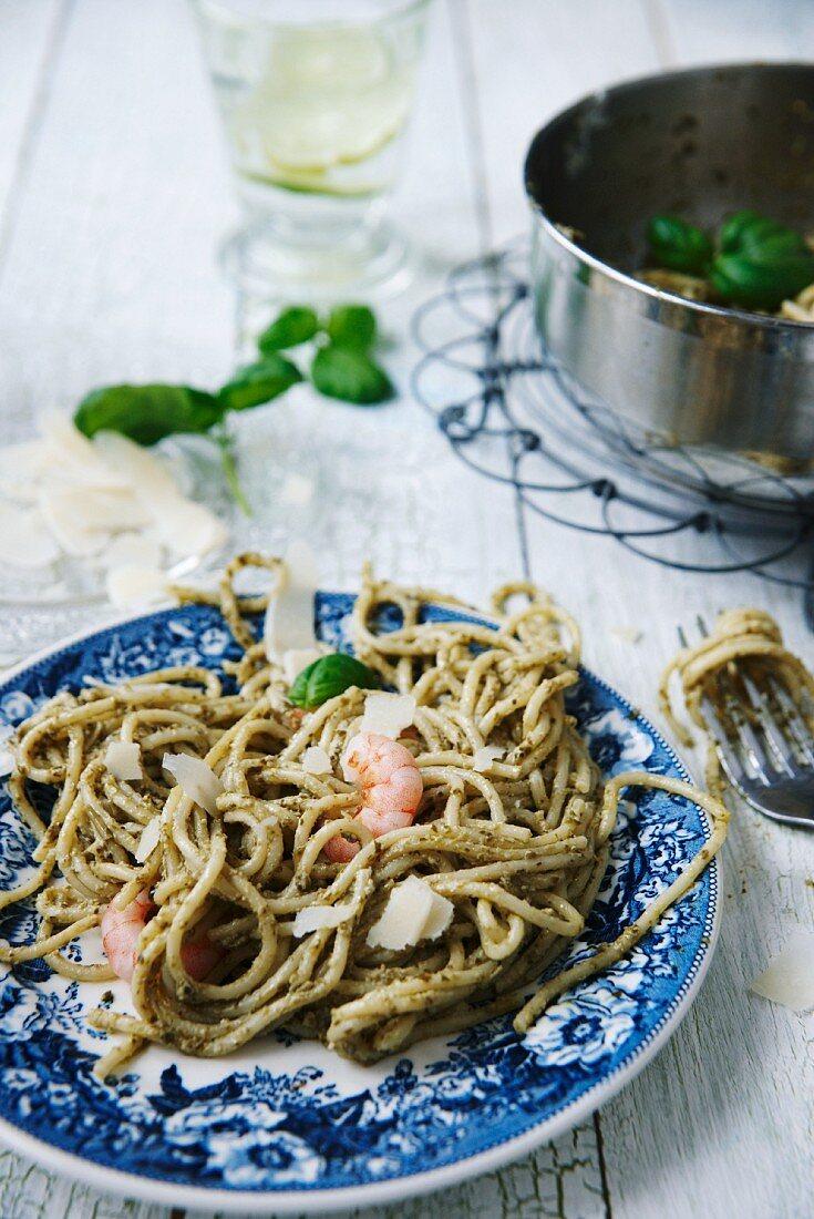 Spaghetti with green pesto, prawns, parmesan and basil leaves