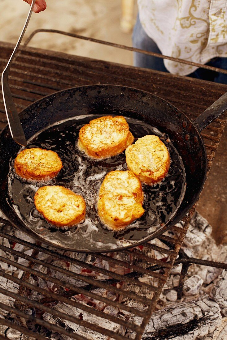 Baguette slices coated in egg yolk being fried in a pan on a barbecue