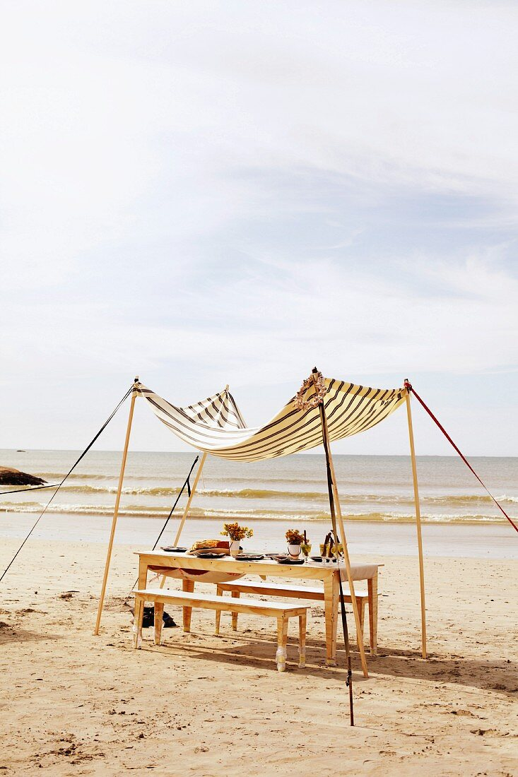 A table laid for a meal under a sunshade on the beach