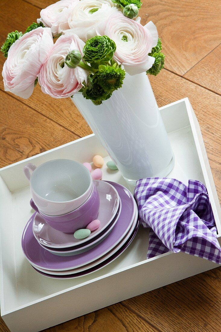 A bunch of spring flowers in a vase alongside a stack of side plates and coffee cups
