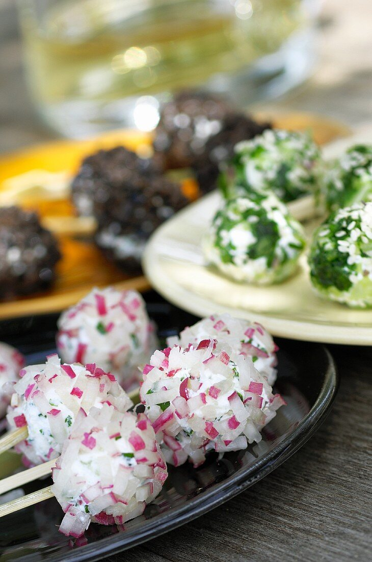 Three types of cheese in balls: with radishes, with herbs and with black olives