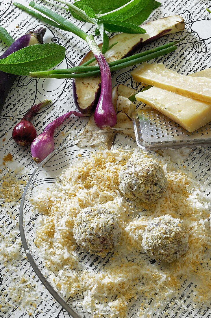 Vegetable balls tossed in a mixture of breadcrumbs and grated cheese, ready to be cooked