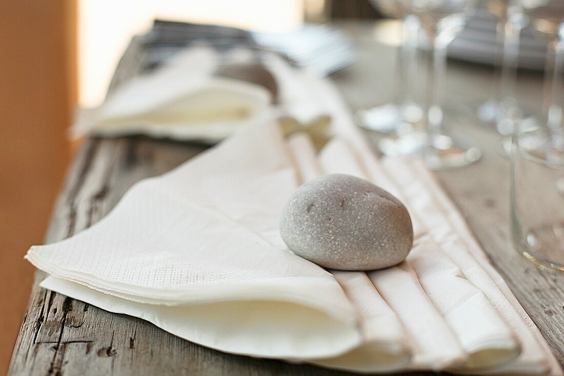 Paper napkins weighed down with a stone on a table outdoors