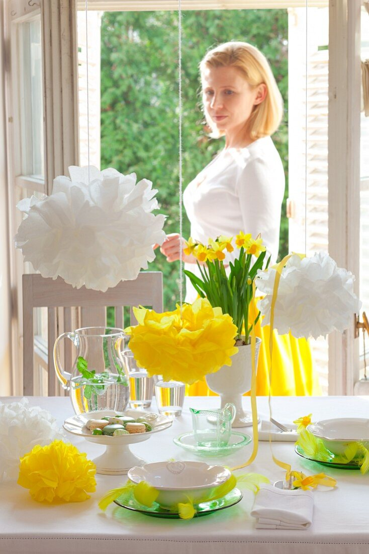 A woman looking at a table laid for Easter celebrations, with narcissi and pompoms