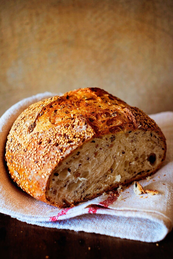 Seeded bread, sliced open, on a linen cloth