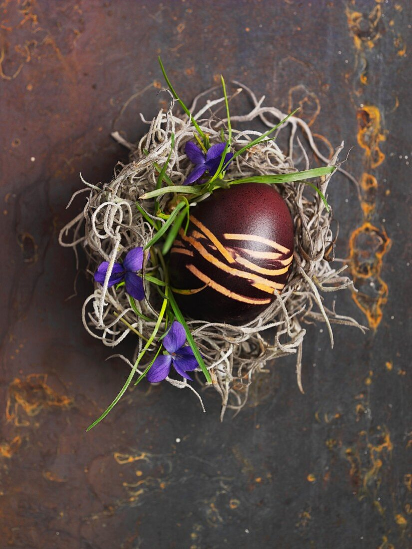 An egg painted in shades of brown for Easter, in a nest (view from above)
