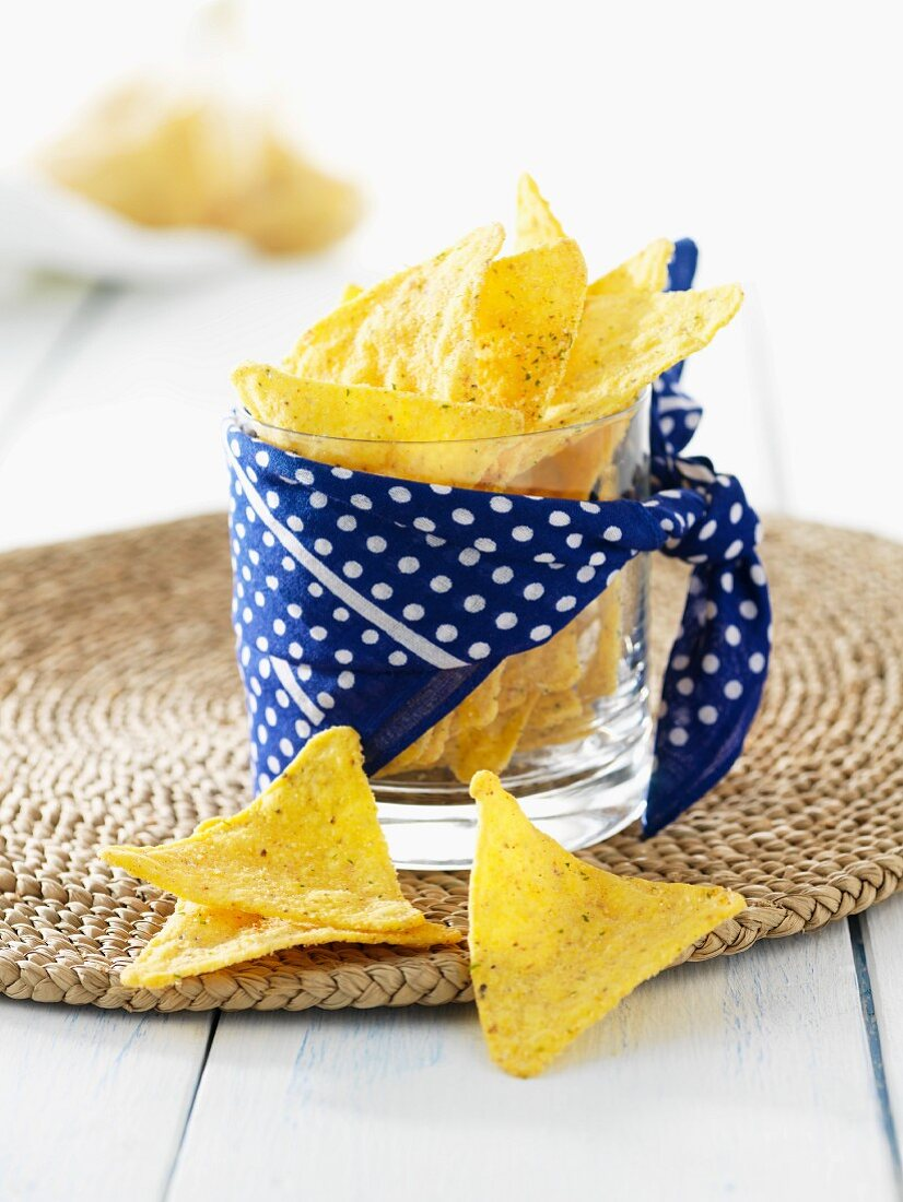 Ranch flavour tortilla chips in a glass wrapped with a spotted cloth