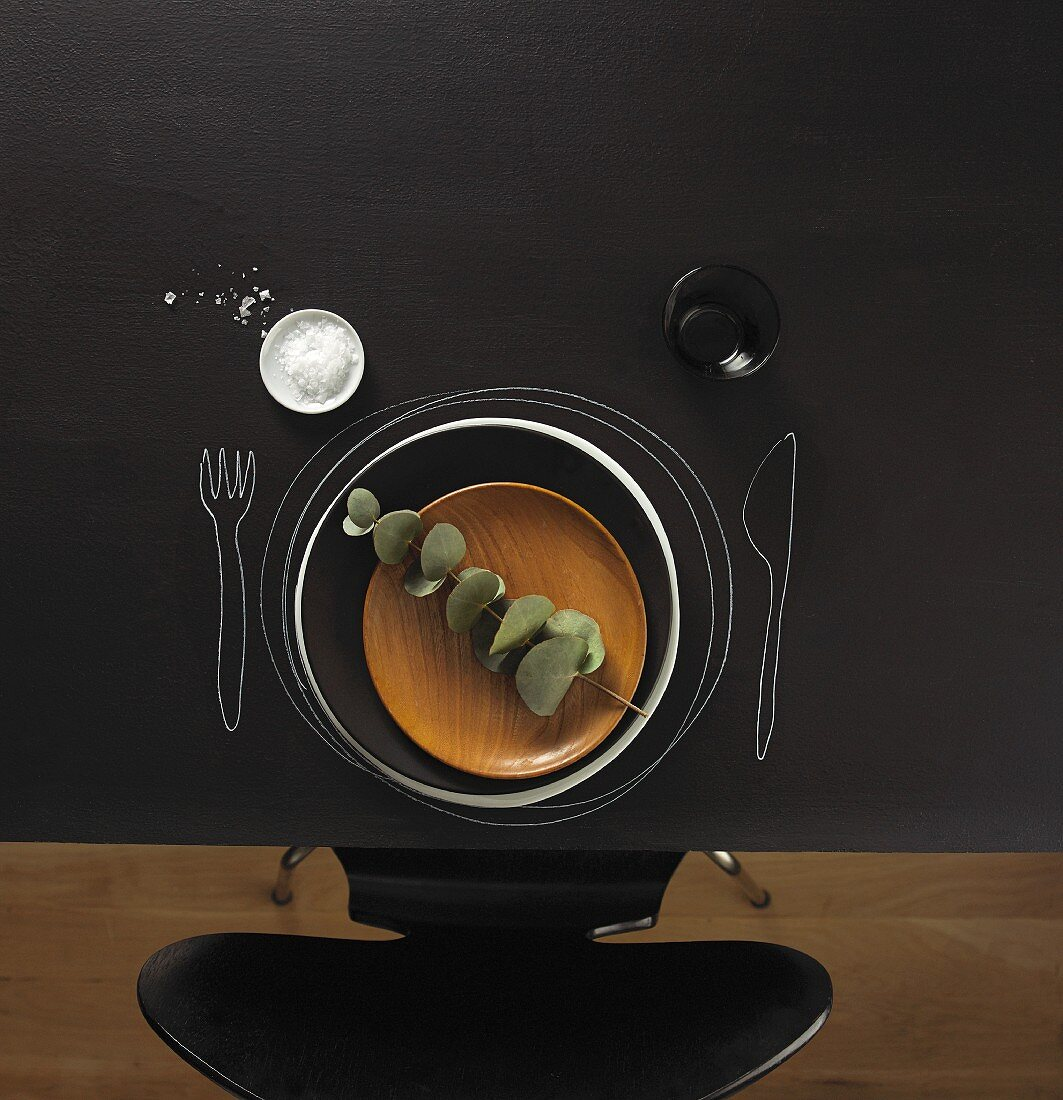 A place set at a blackboard table with a wooden plate, salt and a wine glass