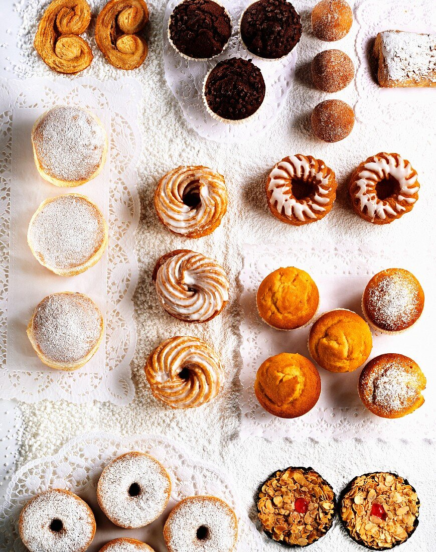 Assorted cakes and pastries on paper doilies