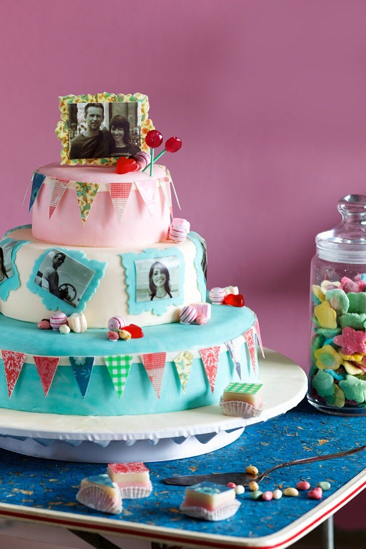 A bright wedding cake decorated with photos and colourful bunting