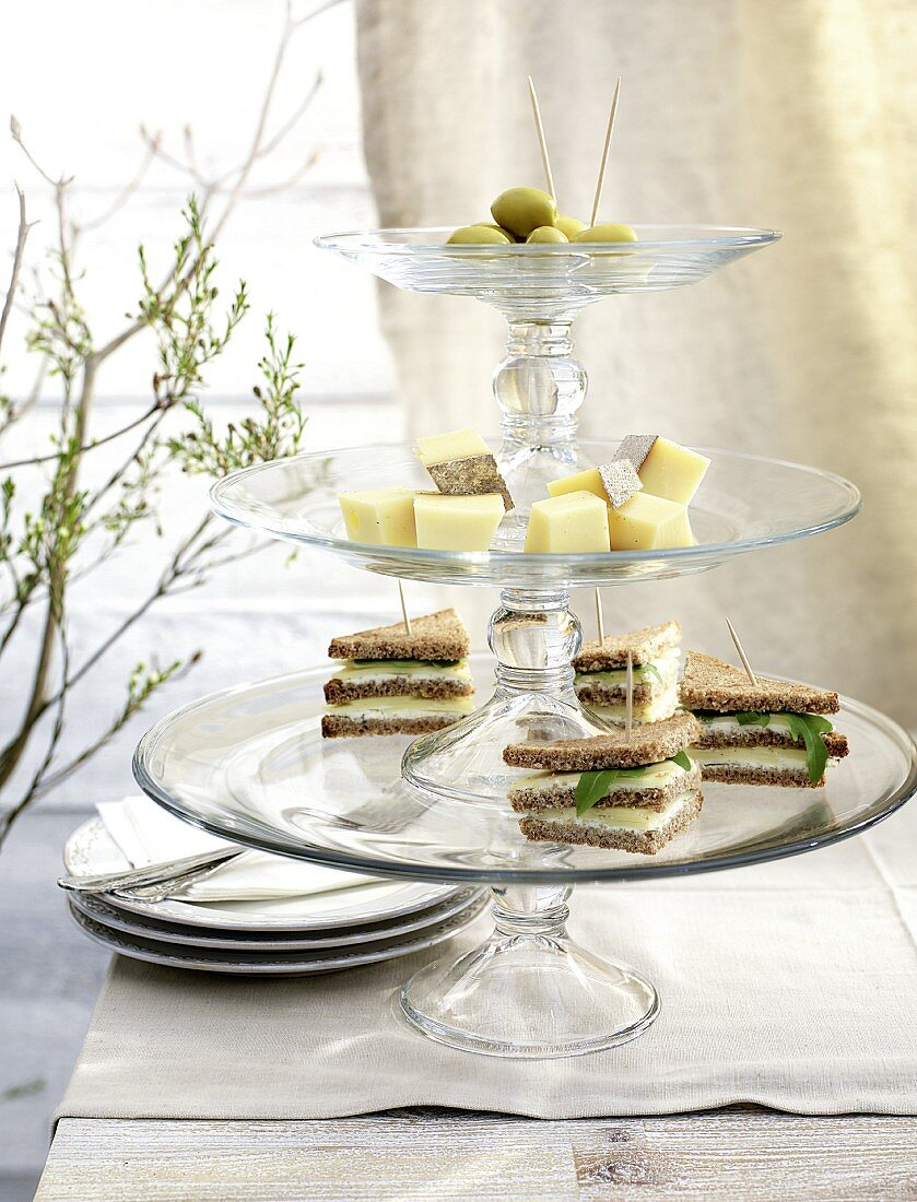 Triangular cheese sandwiches, cubes of cheese and olives on a cake stand
