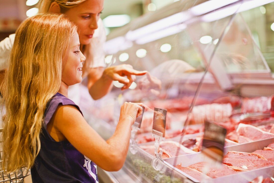 A mother and daughter at the meat counter in a supermarket