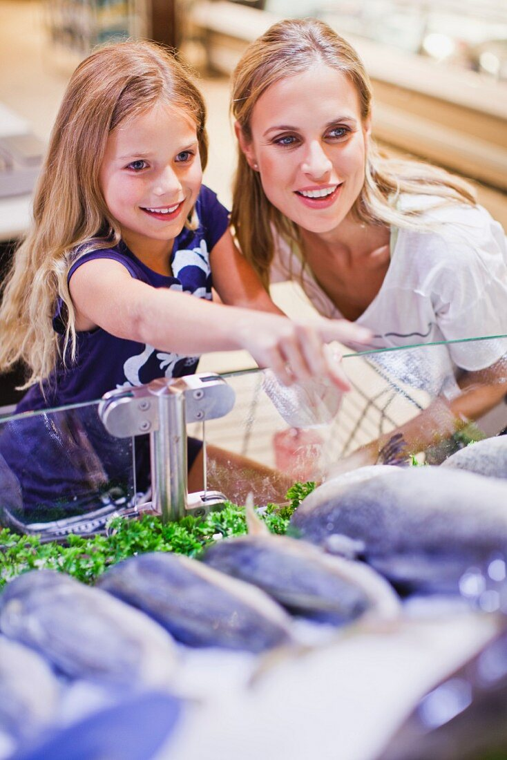 A mother and daughter at the fish counter in a supermarket