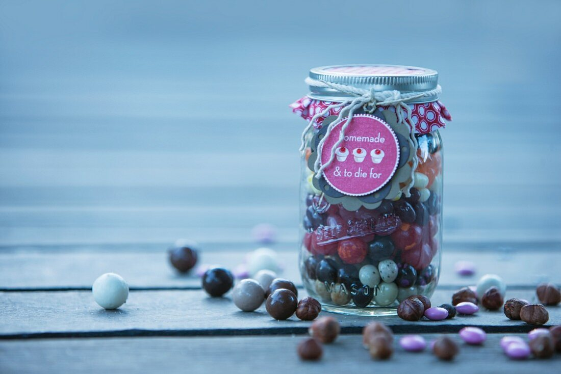 Assorted sweets (jelly beans, liquorice and chocolate drops) in a jar as a gift