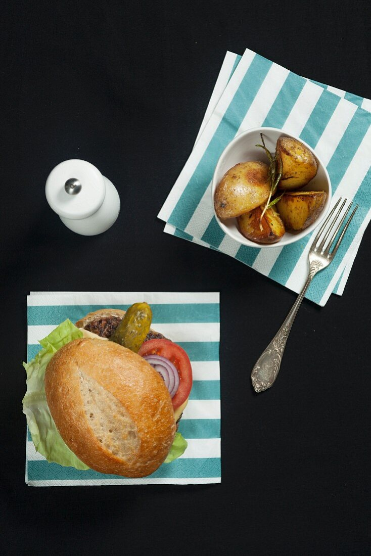 A hamburger with lettuce, tomato and gherkin, served with rosemary potatoes