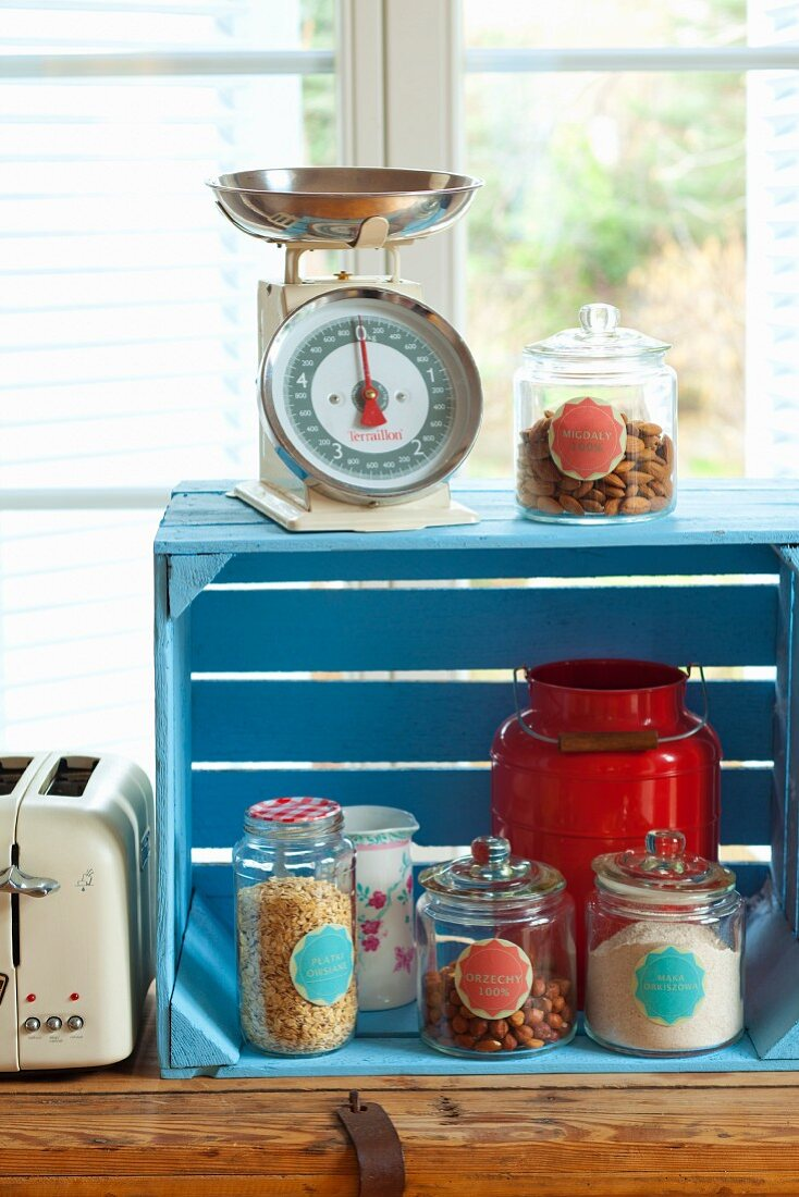 Storage jars in a wooden crate, containing rolled oats, hazelnuts and spelt flour; kitchen scales and a toaster