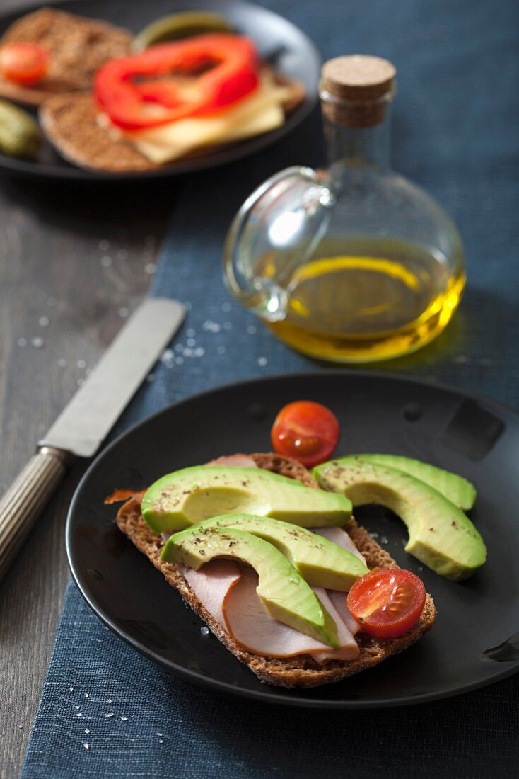 A slice of bread topped with ham, with avocado and tomatoes, and a slice of bread topped with cheese and peppers