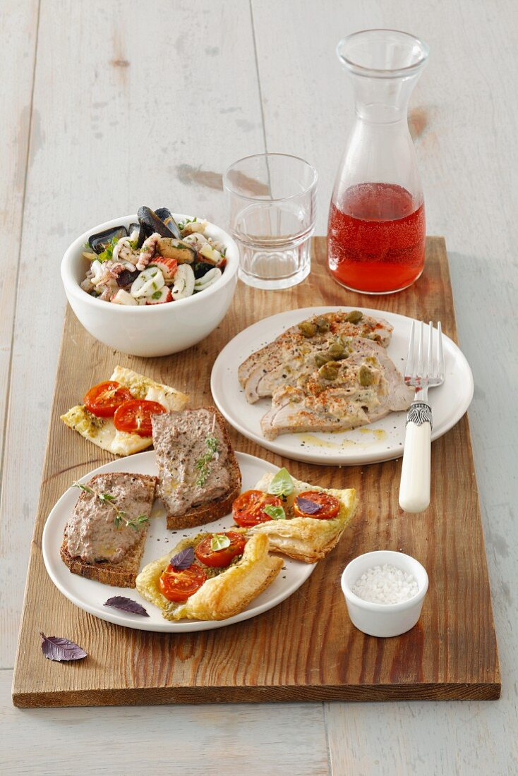 Four assorted Italian starters on a wooden board