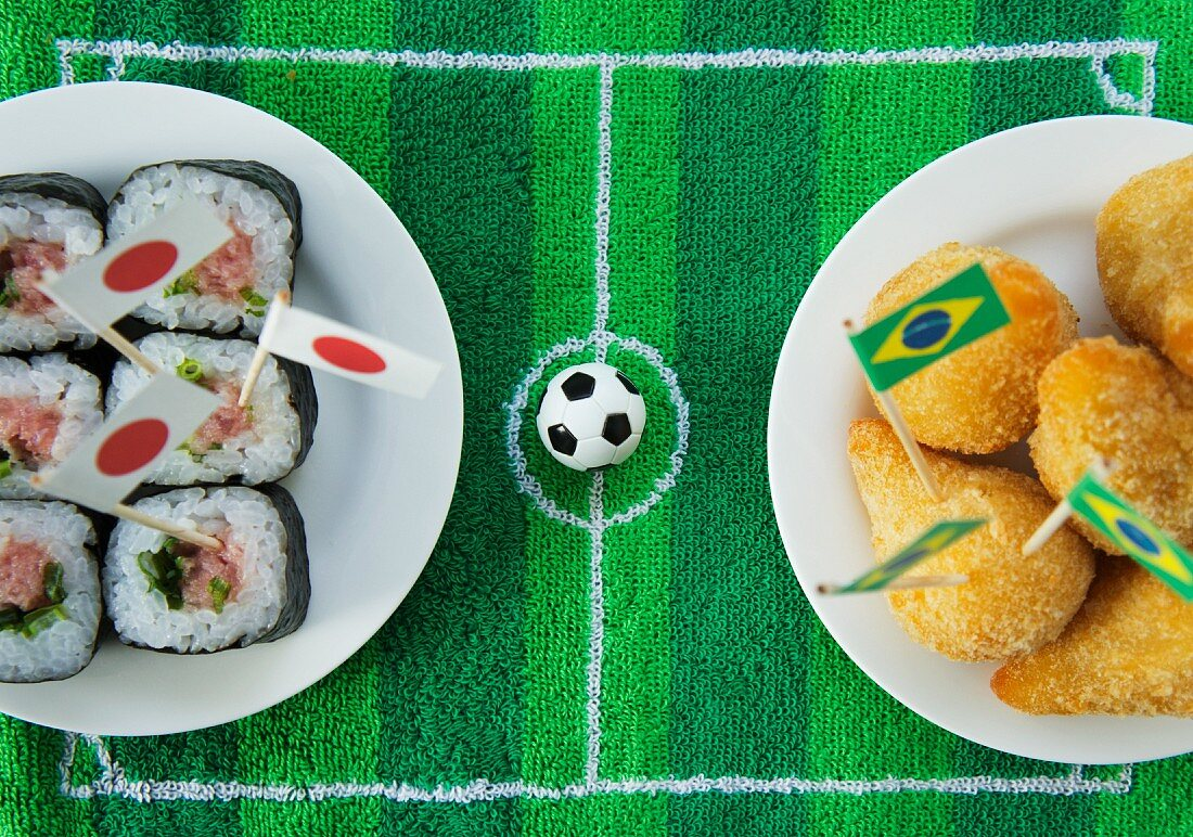 Sushi (Japan) and salgadinhos (Brazil) with football-themed decoration