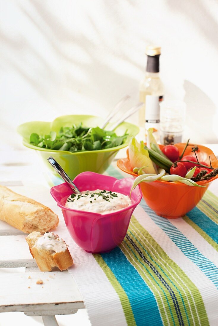Crudités, salad and pieces of baguette on a garden table