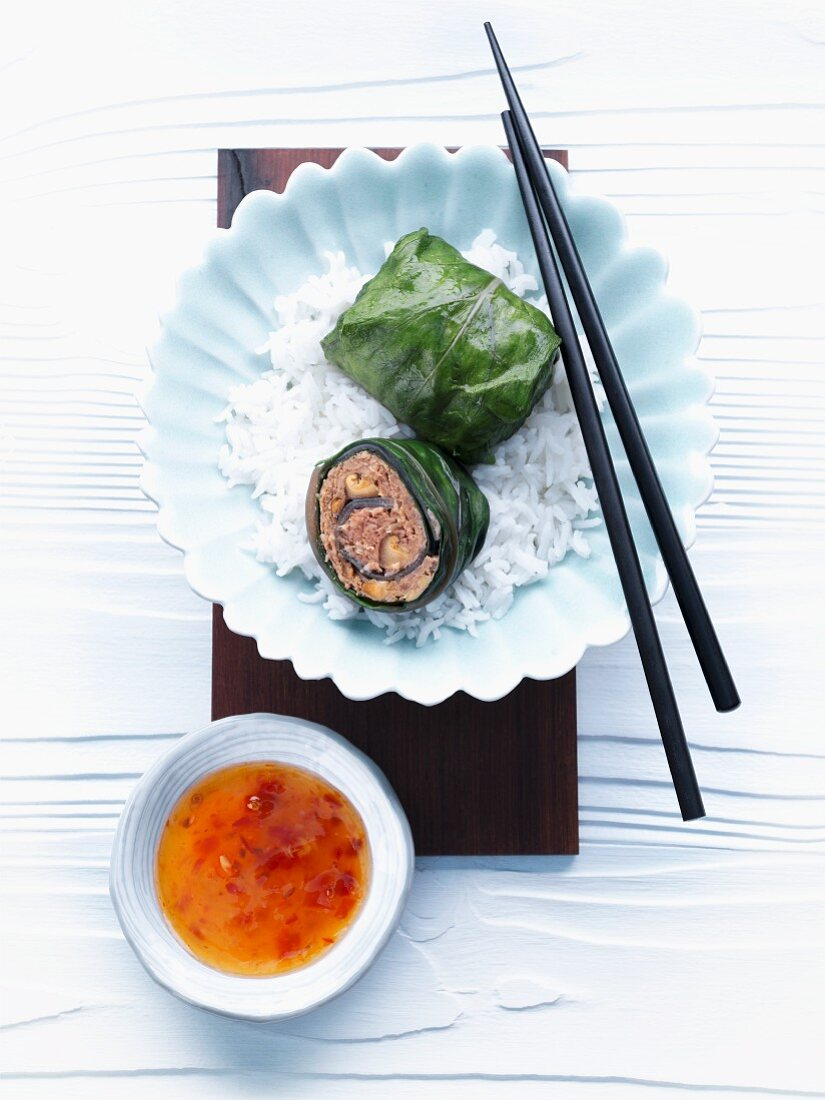 Chard rolls with an Asian-style filling on a bed of rice with sweet chilli sauce