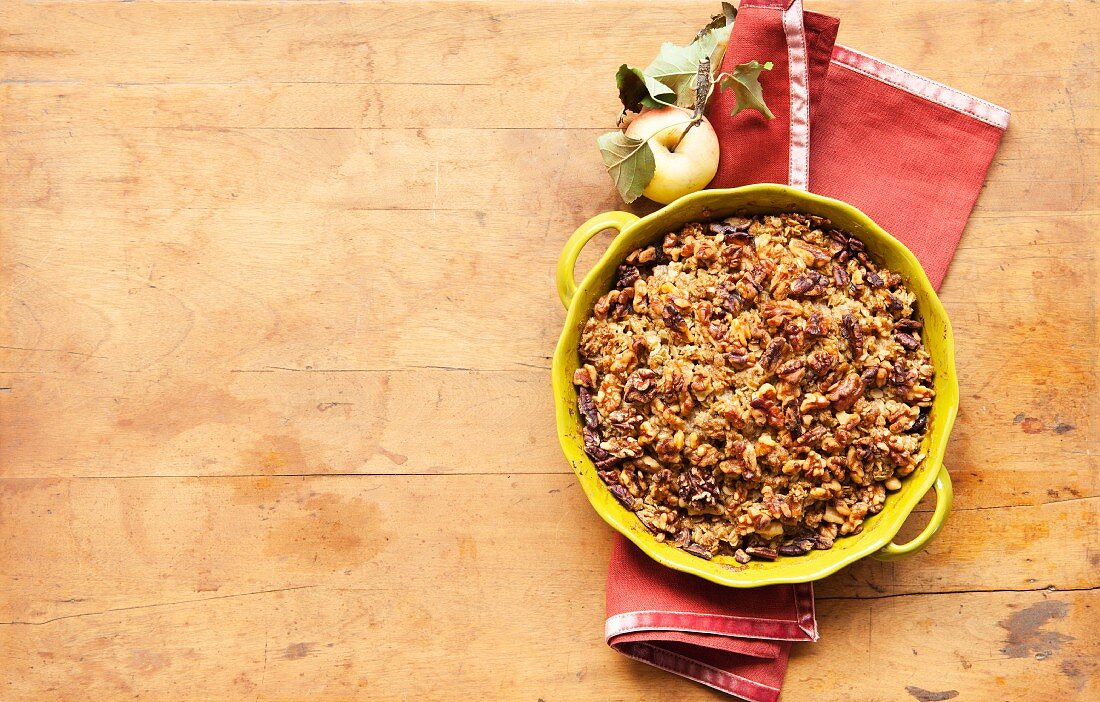 Gluten Free Apple Crisp in a Baking Dish with a Fresh Apple