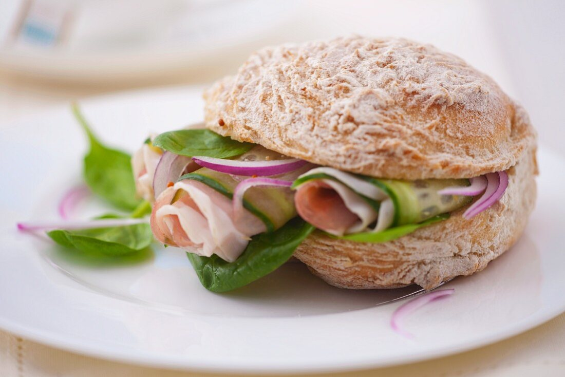 A sandwich filled with spinach, prosciutto, cucumber and onions
