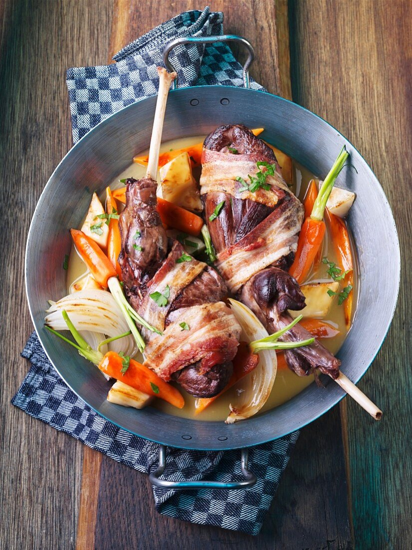 Hare's leg wrapped in bacon on a bed of vegetables