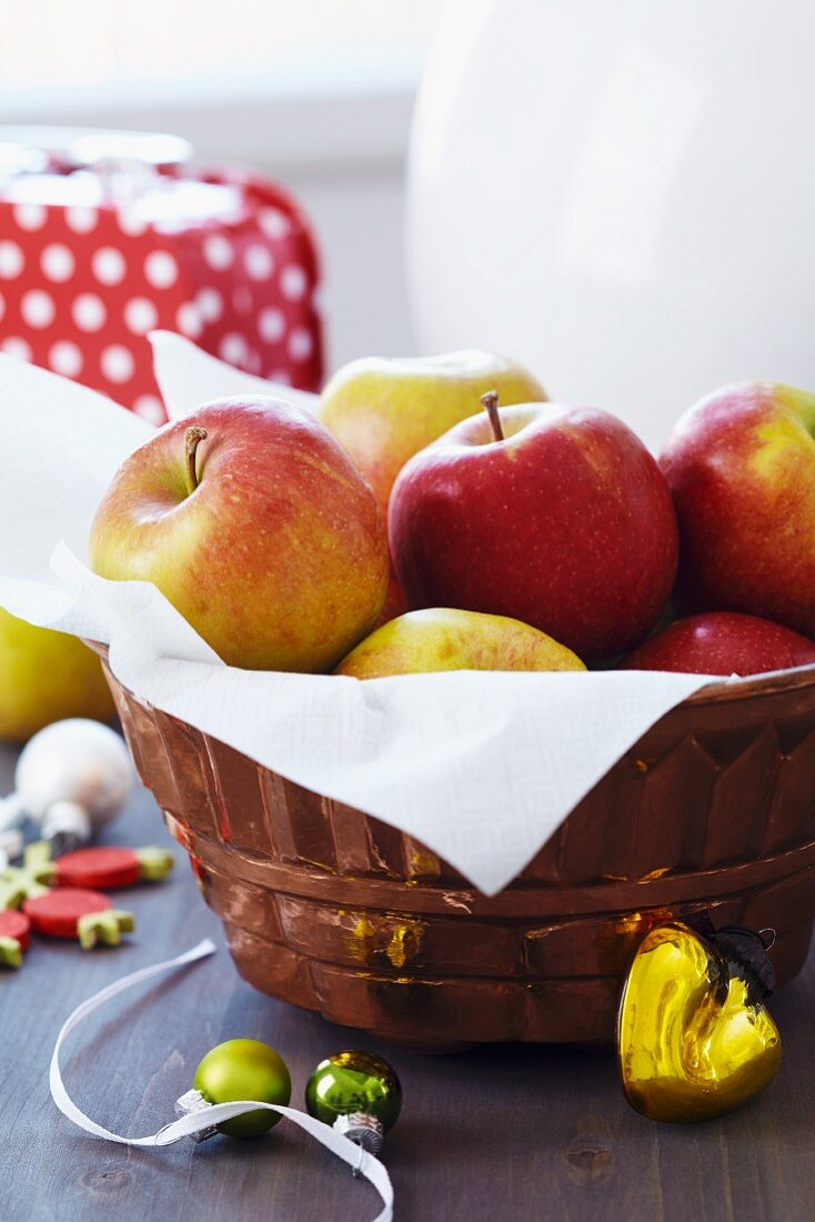 Apples in copper jelly mould used as fruit basket and Christmas decorations