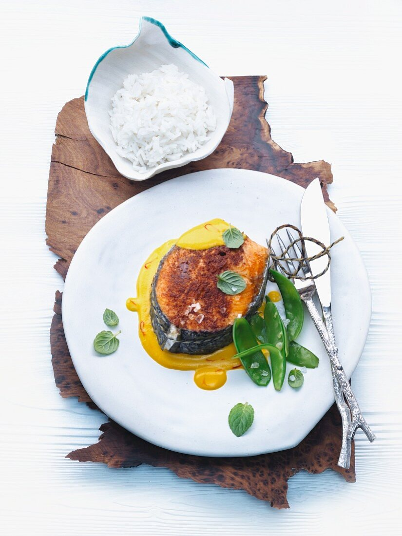 Tandoori salmon cutlet with saffron sauce, sugar snap peas and rice