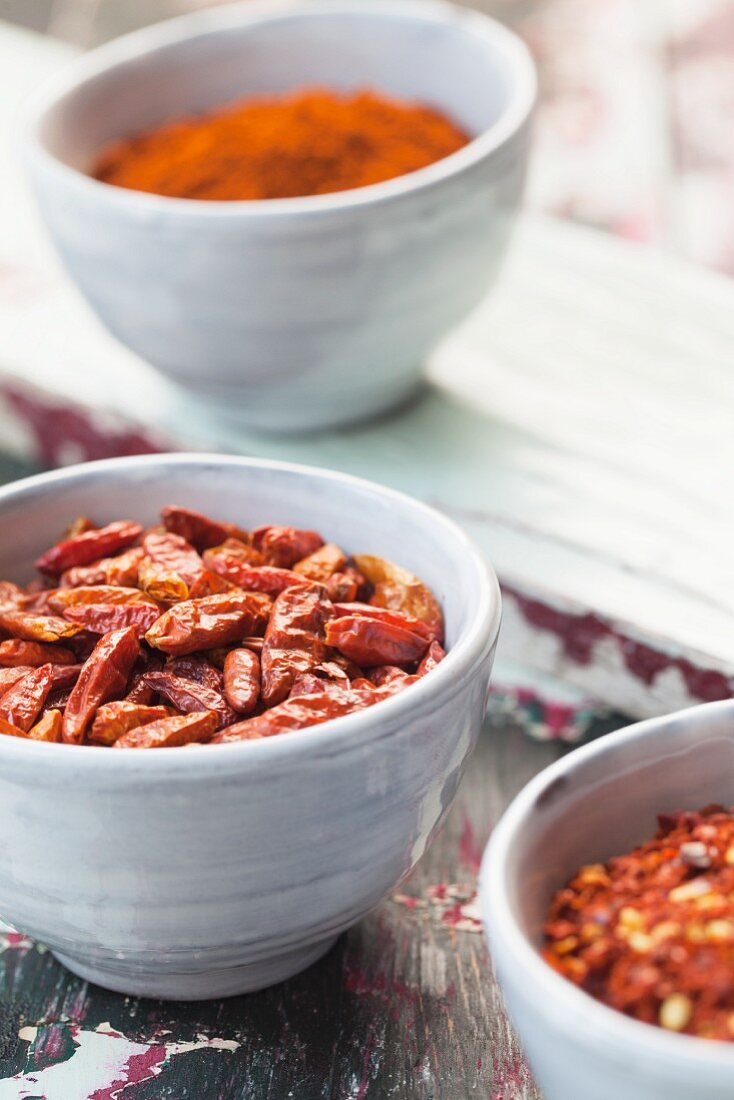 Whole, dried chilis and chili powder in dishes on a colorful wooden surface